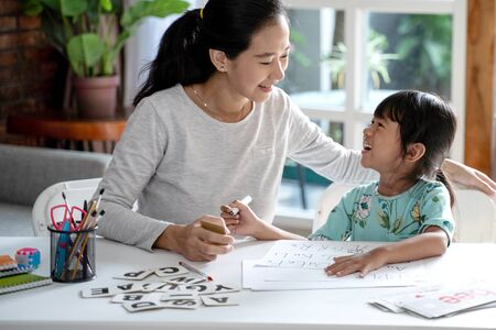 Photo pour mother teaching her daughter the basic to read and write - image libre de droit