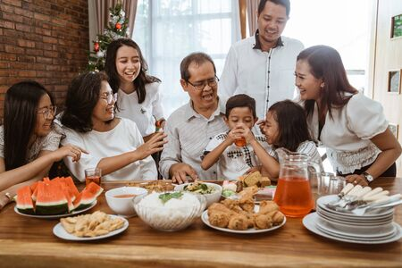 Photo pour family cheering during lunch together at home - image libre de droit
