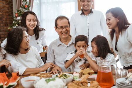 Foto de family fun having lunch with friends in diningroom together - Imagen libre de derechos