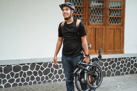 Photo pour smiling asian young man carrying her folding bike - image libre de droit