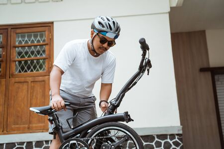 Photo pour Asian mens sunglasses try folding his folding bike to get ready to go to work - image libre de droit