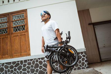 Photo pour asian young man walking and carrying her folding bike - image libre de droit