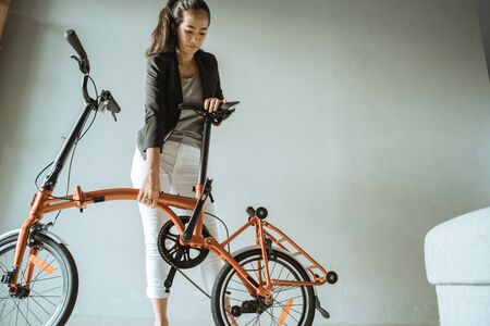 Photo pour asian young woman stand on living room when open fold her folding bike - image libre de droit