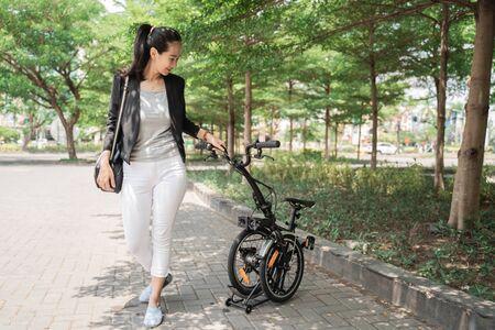 Photo pour asian woman worker holding her folding bike - image libre de droit