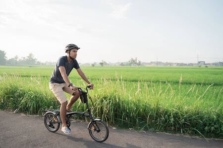 Photo pour Asian young male wear helmets to ride folding bikes in the rice fields - image libre de droit