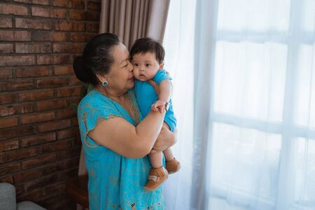 Photo pour asian old woman stand with carrying and kiss little son - image libre de droit