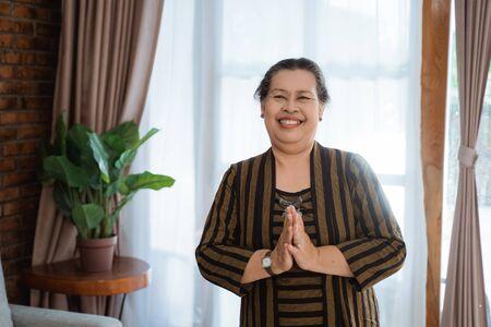 Foto de smile asian old woman woman standing wearing batik lurik - Imagen libre de derechos
