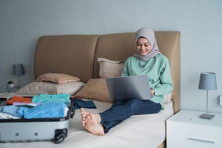 Photo pour Asian muslim woman using laptop to looking departure schedules via online application - image libre de droit