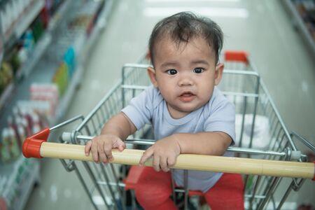 Foto de happy infant baby sitting alone in shopping cart or trolley in grocery supermarket - Imagen libre de derechos