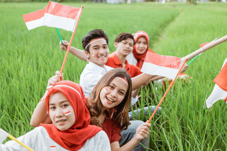 Foto de Asian youth smiles holding small red and white flags sitting in the middle of rice fields - Imagen libre de derechos