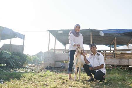 Photo pour muslim couple buy a goat for eid adha sacrifice or idul qurban - image libre de droit