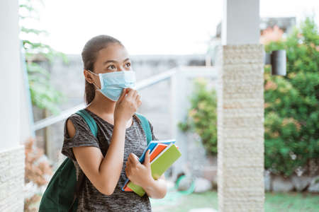 Photo pour Asian student girl wears a mask with backpack take away books - image libre de droit