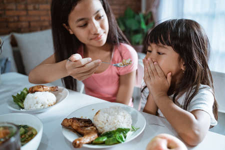 Photo pour Close up of a little girl covering her mouth not want to eat when her older sister feed her food with a spoon - image libre de droit