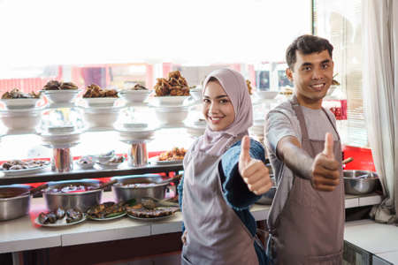 Photo pour portrait of young man and female muslim working as traditional food seller - image libre de droit
