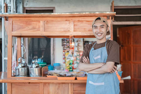 Photo for angkringan seller in apron smiles with crossed hands while standing - Royalty Free Image