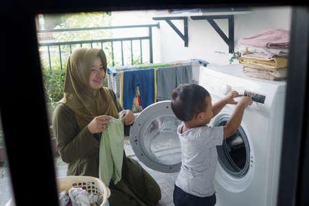 Foto de mother a housewife with a baby engaged in laundry - Imagen libre de derechos