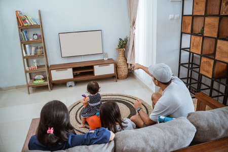 Photo pour Family Sitting On Sofa At Home Watching TV Together - image libre de droit