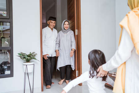 Photo pour asian muslim aged couple meeting kids and grand children at doorstep during eid mubarak - image libre de droit