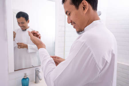 Photo pour muslim asian man looking at mirror and get dressed before going to the mosque - image libre de droit