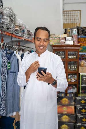 Photo pour Portrait of a young asian muslim man shopping for clothes at store - image libre de droit