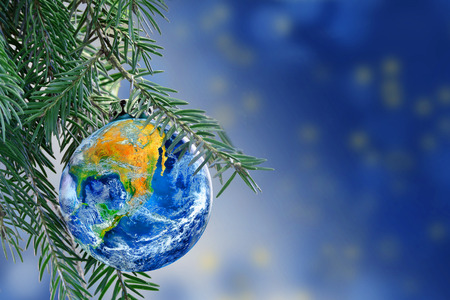 earth globe as a Christmas bauble on fir branch of a christmas tree, Merry Christmas all over the world, copy space.