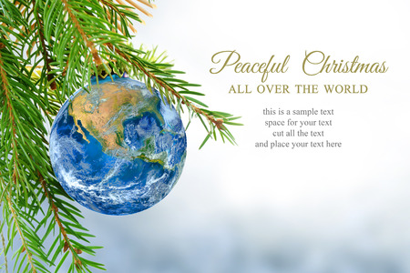 earth globe as christmas ball hanging on fir branch, message: peaceful Christmas all over the world, symbol, metaphor, copy space, bright snowy background.