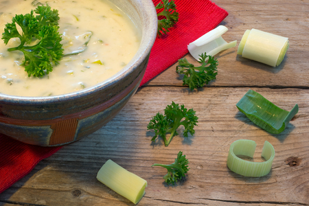 cream sauce in a bowl with fresh leeks and herbs on  rustic wood