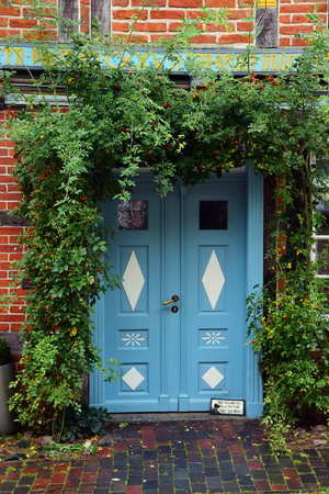 blue painted front door with patterns in a historic half-timbered house with climbing plants at the entrance, typical for northern Germany