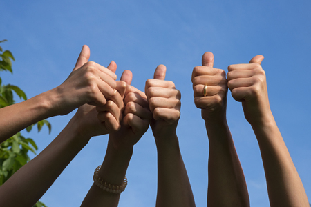 Thumbs up, friends raise their hands and show their thumbs as a positive gesture on a sunny day against the blue sky with copy space