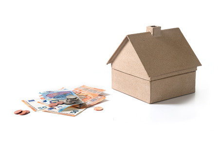 house of cardboard next to euro banknotes and coins, real estate concept for property investment or rental costs for a home, isolated on a white background