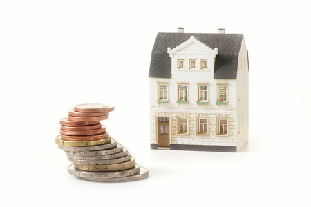 stack of coins next to a miniature old building house, real estate concept for property investment or rental costs for a home, isolated on a white background