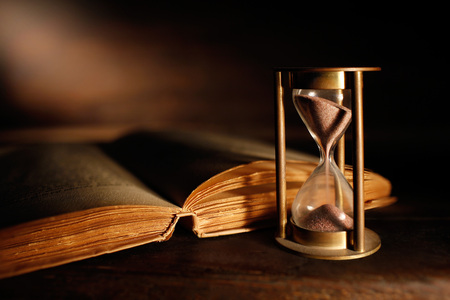 Photo pour old hourglass and ancient book with open pages - image libre de droit