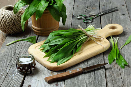 Ramson or wild garlic on a cutting board on a gray table