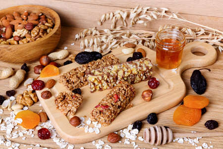 Fitness bars with granola, oatmeal, nuts, dried fruit and honey on the table
