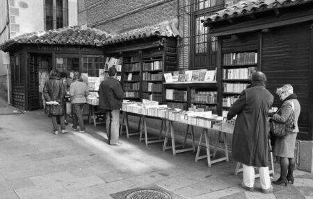 MADRID, SPAIN, November 27: Unidentified people looking at books from the library San Gines in the street on November 27, 2011 in Madrid, Spain.  This library is open from mid-nineteenth century and is characterized also is affixed to the facade of the ch