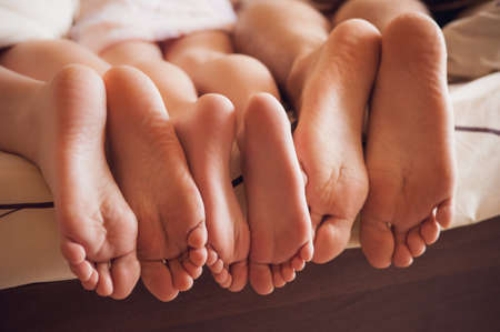 close up of a family showing off their feet under the covers. no faceの写真素材