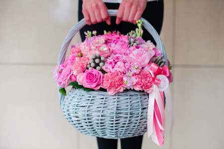 girl holding big beautiful pink bouquet of mixed flowers in basket