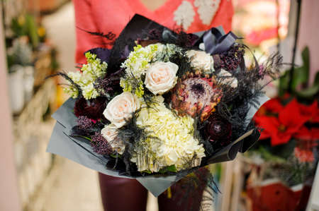 Stylish and elegant winter bouquet of flowers in woman hands. No face, close up photo