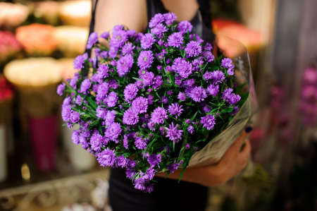 Elegant and beautiful bouquet of little purple flowers in woman hands. No face, close up