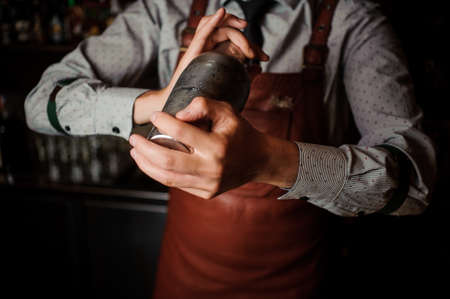 Photo for Barman in a brown apron shaking the shaker on the dark background of bar counter - Royalty Free Image