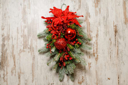 Beautiful Christmas composition for door decorating made of fir tree and red plants and glass balls