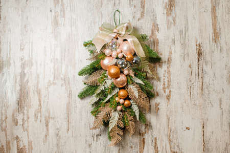 Beautiful Christmas composition for door decorating made of fir tree and glass balls in golden and silver tones