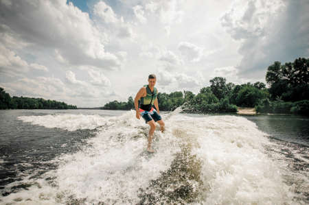 Active athletic surfer riding stylish wake board on high wave of motorboat,performs his professional skills and abilities