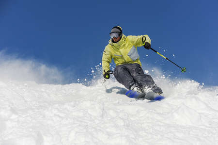 Foto de Skier dressed in yellow and grey sportswear running down the mountain slope on the background of amazing resort Gudauri, Georgia - Imagen libre de derechos