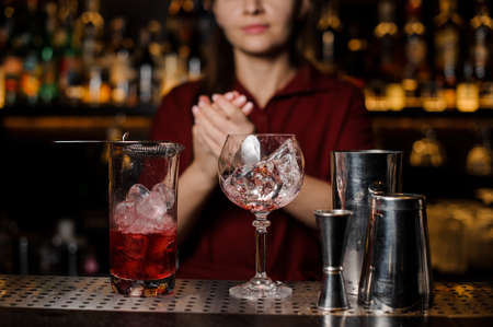 Female bartender making final actions with the light red delicious cocktail before serving it at the bar counter
