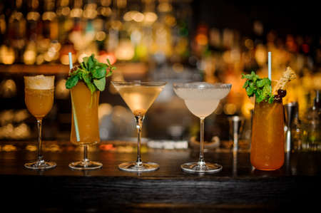 Foto de Set of classic cocktails: Dirty Martini, Sherry Cobbler, Brandy Crusta, Margarita and Cobras Fang arranged on the bar counter - Imagen libre de derechos