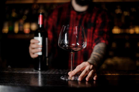 Photo pour Barman with an empty burgunya glass and a bottle of red wine - image libre de droit