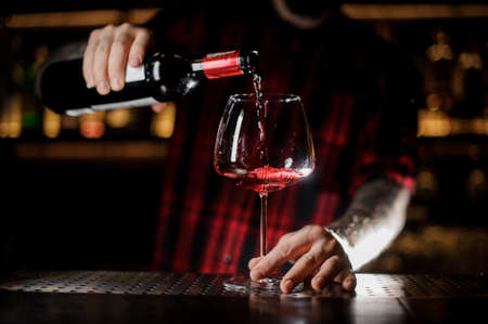 Photo pour Tattooed barman pouring red wine into the burgunya glass - image libre de droit