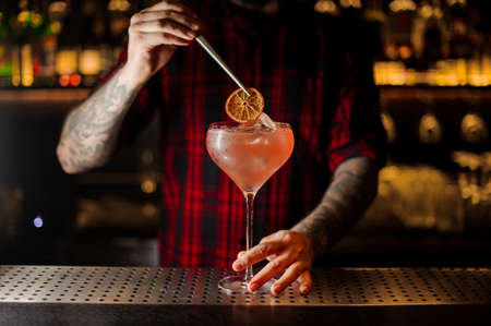Foto de Barman decorating sweet alcoholic cocktail with a slice of dry orange on the bar counter - Imagen libre de derechos