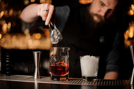 Photo for Bartender adds ice in glass with special ice tongs - Royalty Free Image